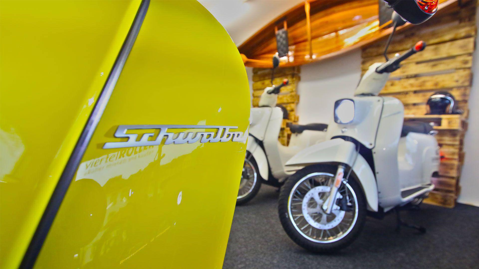 Schriftzug der Firma Schwalbe auf einem gelben Roller, im Hintergrund ein Kanu, zwei Roller und ein Helm, jeweils unscharf gezeichnet